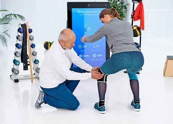 Physiotherapeut korrigiert Patientin vor der Pixformance Station, eHealth, Telereha
