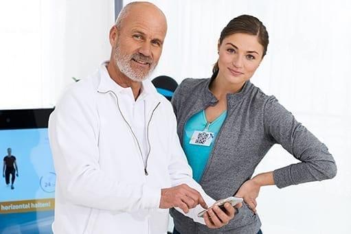 Therapeut und Patientin nutzen die voll vernetzte Pixformance App nach dem Training an der digitalen Pixformance Station