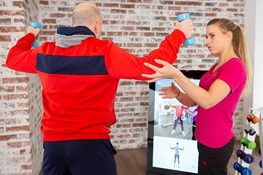 Training in der Physiotherapie Praxis Raum für Gesundheit in Stuttgart. Eine Physiotherapeutin gibt dem Patienten Hilfestellungen, während dieser an der Pixformance Station trainiert.