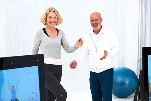 Patientin lächelnd macht eine Übung auf dem Stepper, der Physiotherapeut steht, ebenfalls lächelnd, neben ihr und gibt Anweisungen mit seinen Händen. Links ist ein Ausschnitt der Pixformance Station zu erkennen. Physiotherapie Marketing.