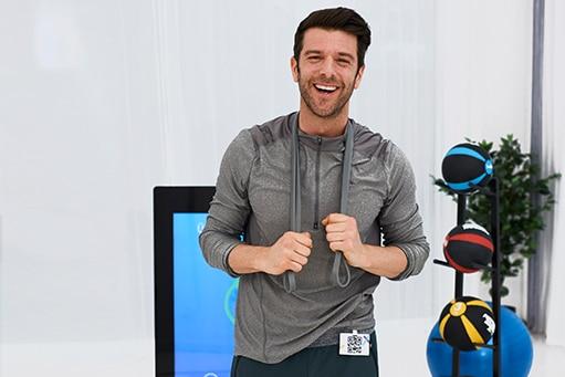Patient lachend mit dunkelgrauem Oberteil und einem Fitnessband um die Schultern. Im Hintergrund ist die Pixformance Station zu sehen. Physiotherapie Marketing.