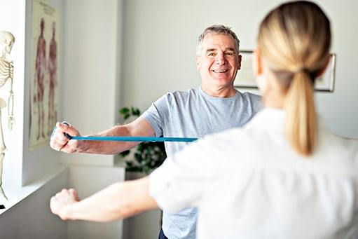 Glücklicher Patient im höheren Alter macht eine Übung mit dem Fitnessband, welche ihm die Physiotherapeutin, die auf dem Bild nur von hinten zu sehen ist, vor macht. Physiotherapie Marketing.