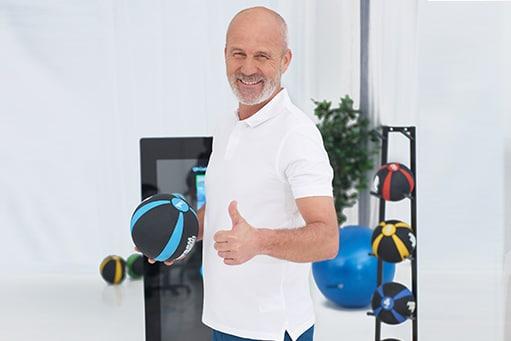 Physiotherapie Umsatz steigern: Jetzt ist der richtige Zeitpunkt, um den Selbstzahlerbereich aufzubauen. Physiotherapeut mit weißem Poloshirt zeigt den Daumen nach oben.
