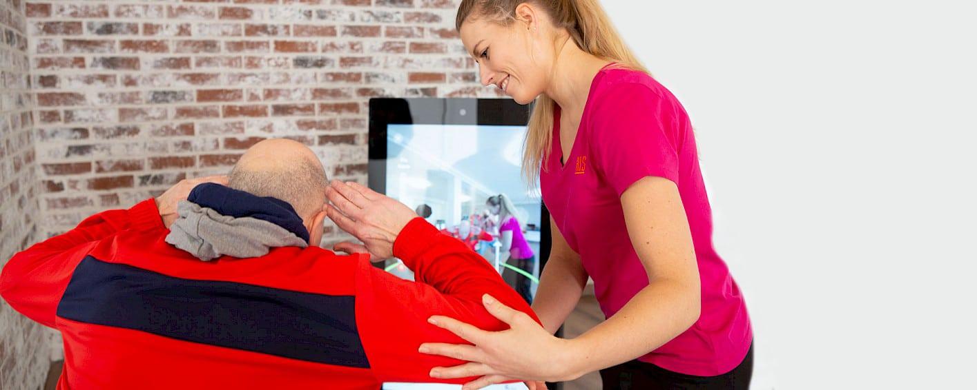 Physiotherapeutin betreut Patient beim digitalen Training an der Pixformance Station