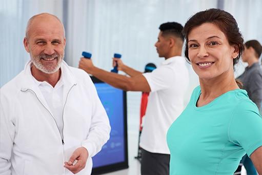 Physiotherapie Unterstützung: Zwei Physiotherapeuten, eine Frau mit türkisem Oberteil und ein Mann mit weißer Jacke grinsend im Vordergrund. Im Hintergrund sieht man Menschen an den Pixformance Stationen trainieren.