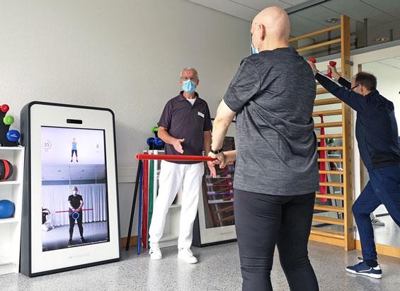 Patienten trainieren vom Therapeuten betreut an der Pixformance Station 1.0