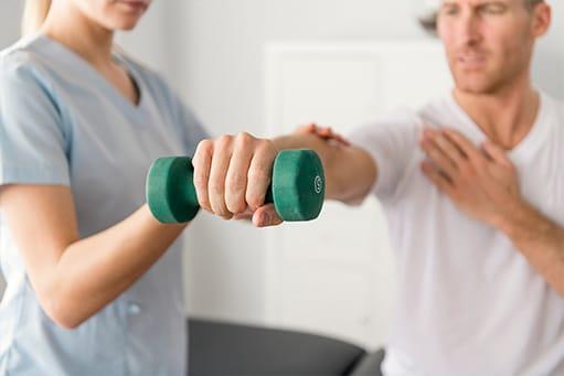 Physiotherapeutin trainiert mit Patienten mit einer Hantel