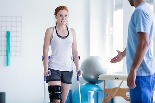 Junge Patientin mit einer Knieverletzung grinsend auf ihre Krücken gestützt mit einem Physiotherapeuten unscharf im Vordergrund, der ihr mithilfe von Gesten etwas erklärt