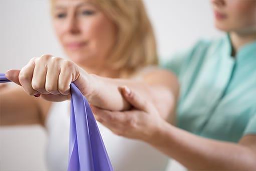 Physiotherapeutin trainiert mit einer älteren Patientin mit blonden Haaren und einem violetten Fitnessband zur Bewegungsaktivierung